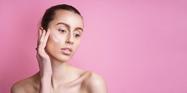 Mulher jovem e bonita aplicando creme no rosto em rosa