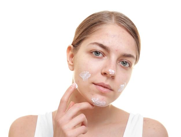 Mulher jovem e bonita aplicando creme para pele com problema no rosto, em fundo branco