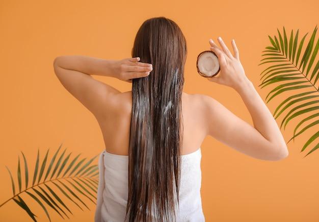Mulher jovem e bonita aplicando óleo de coco no cabelo contra a cor
