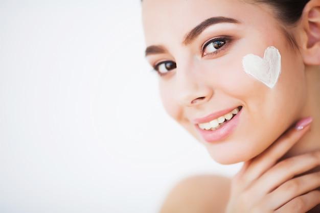Mulher jovem e bonita aplicar creme hidratante no rosto