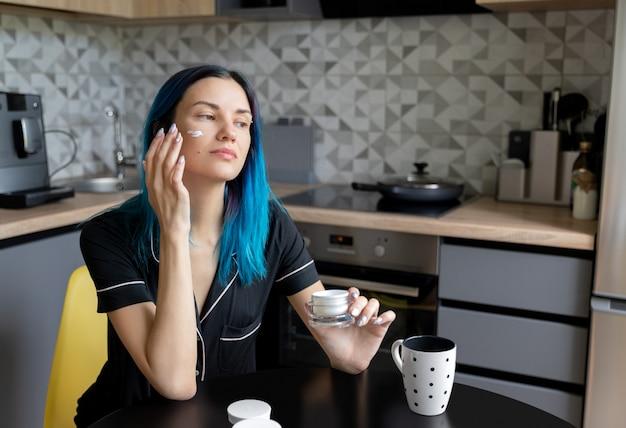 Mulher jovem e bonita aplicar creme no rosto na cozinha moderna