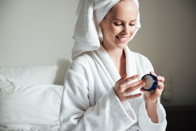 Mulher jovem e bonita aplicar loção para o corpo depois do banho