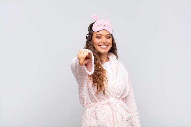 Mulher jovem e bonita apontando de pijama