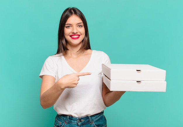 Mulher jovem e bonita apontando ou mostrando e segurando pizzas para levar e segurando pizzas para levar