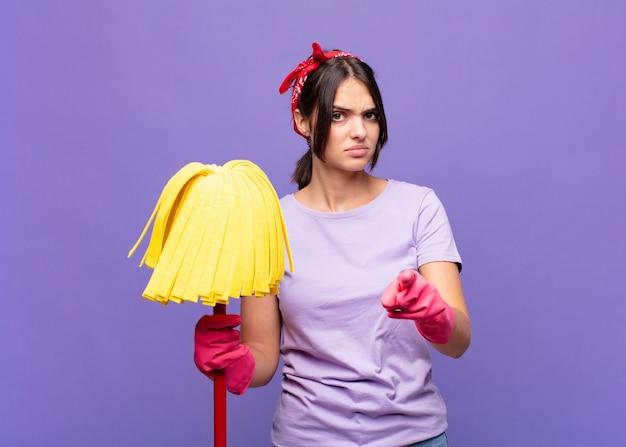 Mulher jovem e bonita apontando para a câmera com os dois dedos e uma expressão de raiva, dizendo para você cumprir seu dever