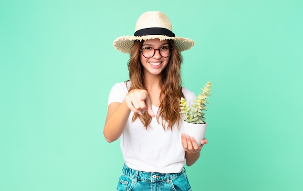 Mulher jovem e bonita apontando para a câmera, escolhendo você com um chapéu de palha e segurando um cacto