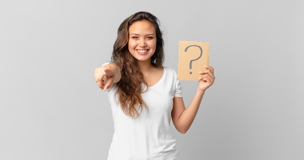 Mulher jovem e bonita apontando para a câmera, escolhendo você e segurando um sinal de interrogação
