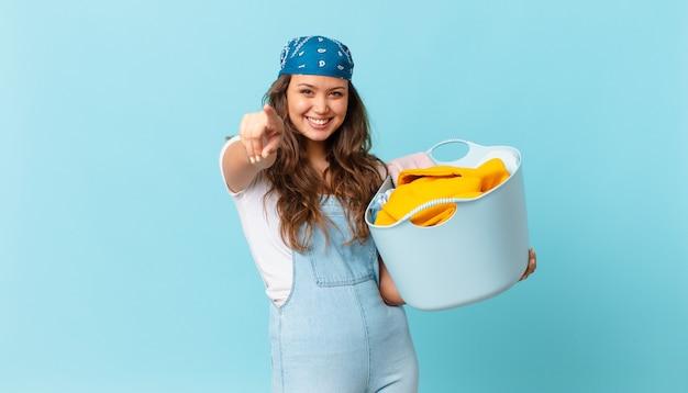 Mulher jovem e bonita apontando para a câmera escolhendo você e segurando uma cesta de lavar roupas
