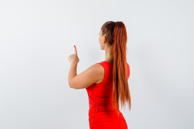Mulher jovem e bonita apontando para cima em um top vermelho, calças e olhando com foco, vista traseira.