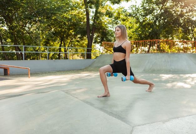Mulher jovem e bonita apta a fazer exercícios matinais com halteres ao ar livre.
