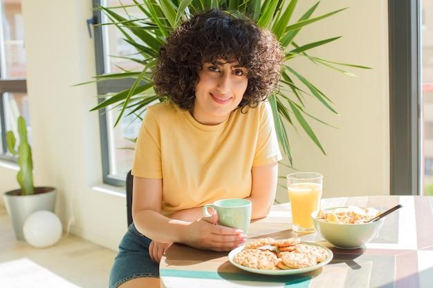 Mulher jovem e bonita árabe tomando um café da manhã em casa.