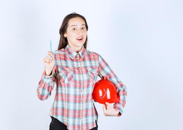 Mulher jovem e bonita arquiteto segurando capacete de segurança com caneta.