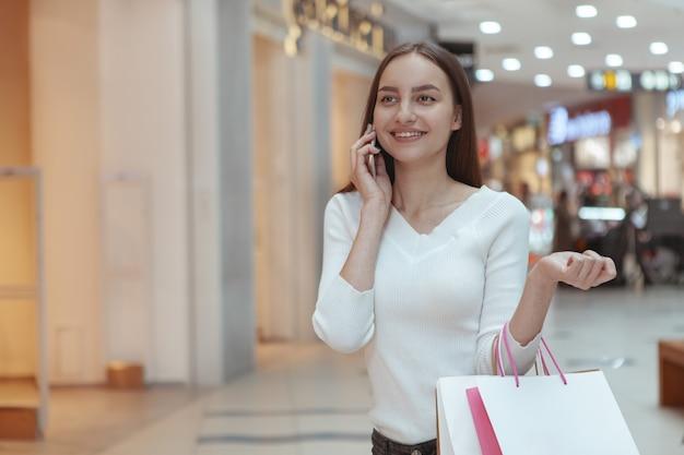 Mulher jovem e bonita às compras no shopping local