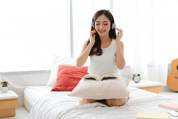 Mulher jovem e bonita ásia relaxar ouvindo música com fones de ouvido na cama em casa