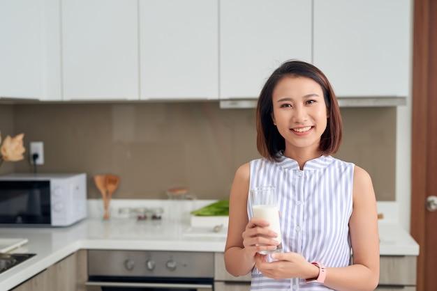 Mulher jovem e bonita asiática bebendo leite na cozinha em casa.