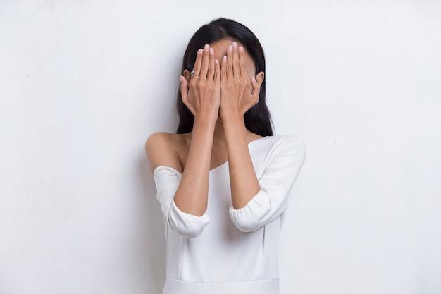 Mulher jovem e bonita asiática cobre o rosto com as mãos no fundo branco