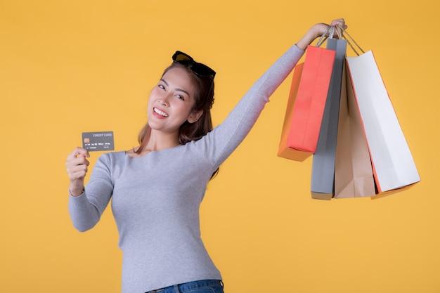 Mulher jovem e bonita asiática com sacolas de compras coloridas e cartão de crédito isolado na parede amarela