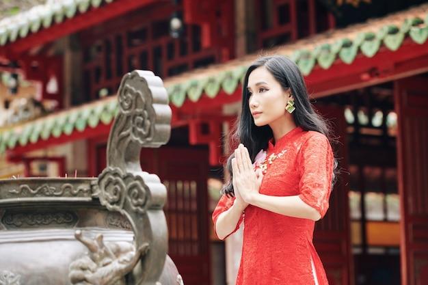 Mulher jovem e bonita asiática com vestido de renda vermelha fazendo gestos de oração em pé na antiga urna de bronze com incensos no templo budista