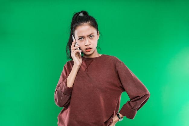 Mulher jovem e bonita asiática falando ao telefone com uma expressão de raiva isolada no fundo verde