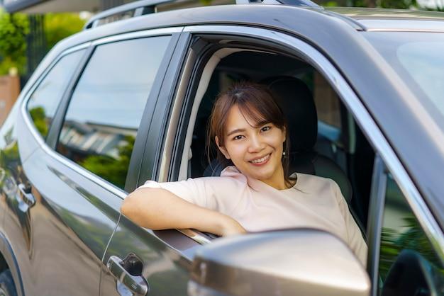Mulher jovem e bonita asiática feliz dirigindo um carro