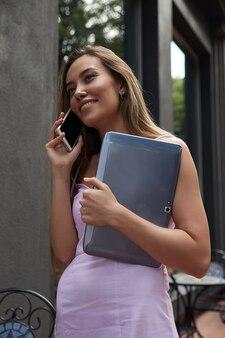 Mulher jovem e bonita asiática no vestido rosa com cabelo comprido escuro, em pé ao ar livre com o laptop, ligando pelo smartphone. estudante descansando fora do café. trabalho distante, comunicação moderna, trabalho remoto