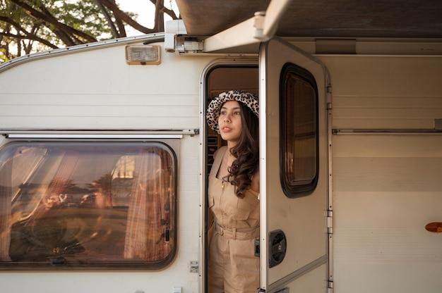 Mulher jovem e bonita asiática passeando em um trailer em um acampamento de férias