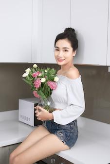 Mulher jovem e bonita asiática posando com flores na cozinha.