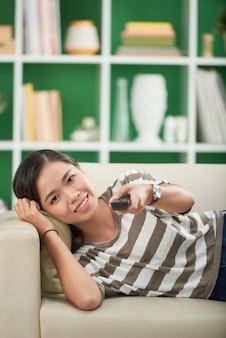 Mulher jovem e bonita asiática relaxando no sofá em casa e assistindo documentário na tv