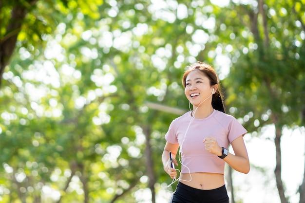 Mulher jovem e bonita asiática saudável correndo no parque pela manhã. conceito de cuidados de saúde.