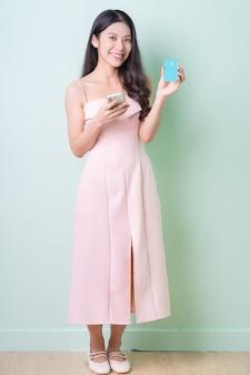 Mulher jovem e bonita asiática segurando um cartão do banco sobre fundo verde