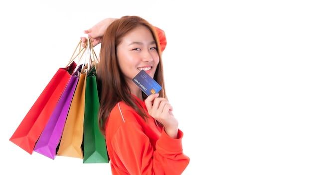 Mulher jovem e bonita asiática segurando uma sacola de compras e mostrando um cartão de crédito para compras de pagamento isolado no fundo branco - copie o espaço