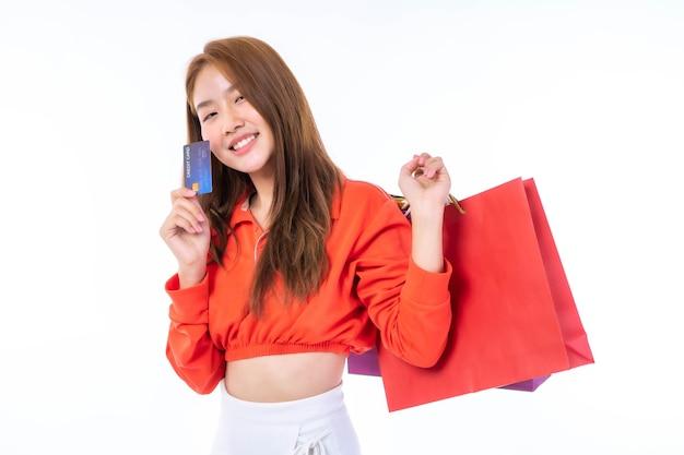 Mulher jovem e bonita asiática segurando uma sacola de compras e mostrando um cartão de crédito para compras de pagamento no fundo branco