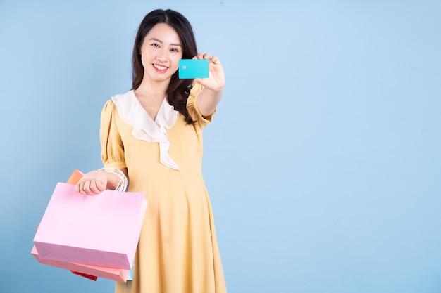 Mulher jovem e bonita asiática segurando uma sacola de compras sobre fundo azul