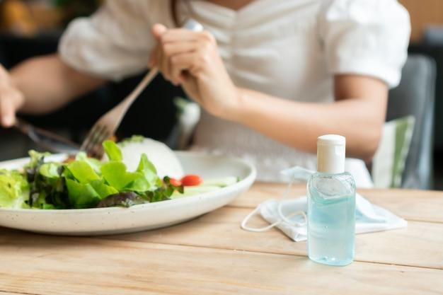 Mulher jovem e bonita asiática tem kunch com gel desinfetante e máscara cirúrgica na mesa de madeira no restaurante. novo estilo de vida normal, conceito de cuidados de saúde.