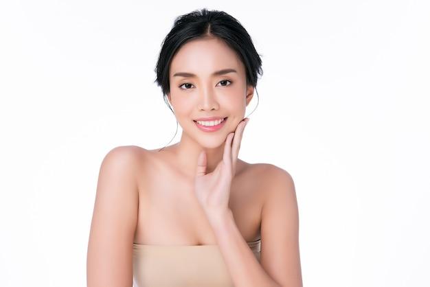 Mulher jovem e bonita asiática tocando a bochecha macia e sorria com a pele limpa e fresca. felicidade e alegria com, beleza e cosméticos conceito,