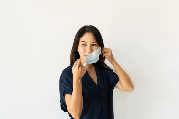 Mulher jovem e bonita asiática usando máscara médica antes de sair de casa. novo conceito de saúde normal. copie o espaço