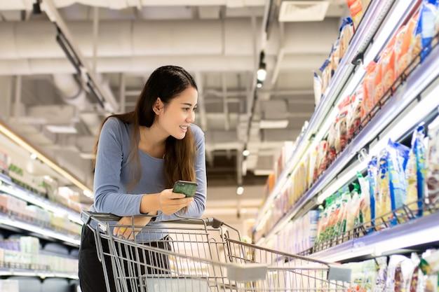 Mulher jovem e bonita asiática usando smartphone e empurrando o carrinho para fazer compras no supermercado.