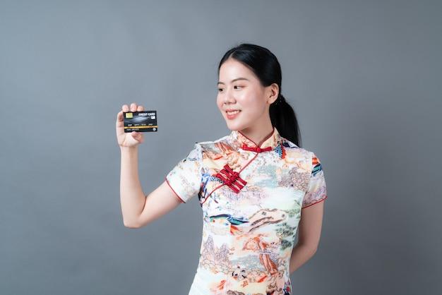 Mulher jovem e bonita asiática usando vestido tradicional chinês com a mão segurando um cartão de crédito no fundo cinza