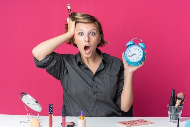 Mulher jovem e bonita assustada sentada à mesa com ferramentas de maquiagem segurando um pincel de pó e despertador colocando a mão na cabeça
