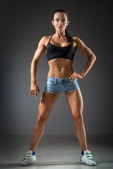 Mulher jovem e bonita atlética com músculos, fazendo exercícios com halteres, musculação na academia