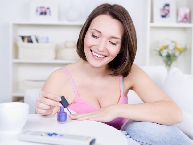 Mulher jovem e bonita atraente com um sorriso feliz, pintando as unhas das mãos