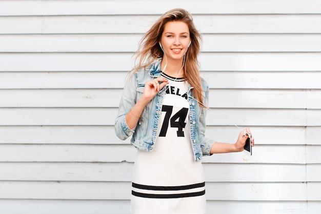 Mulher jovem e bonita atraente em um elegante vestido de verão com uma elegante jaqueta jeans, posando em uma cidade perto de um edifício de madeira vintage. garota americana moderna aproveita o fim de semana e ouve música.