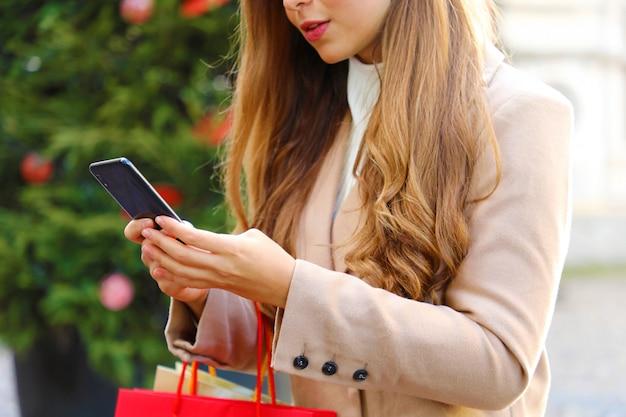 Mulher jovem e bonita atraente usando telefone inteligente para fazer compras on-line e carregar sacolas na época do natal.