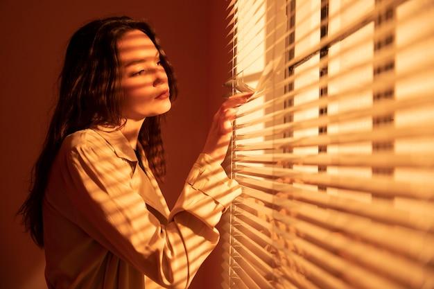 Mulher jovem e bonita atrás das cortinas