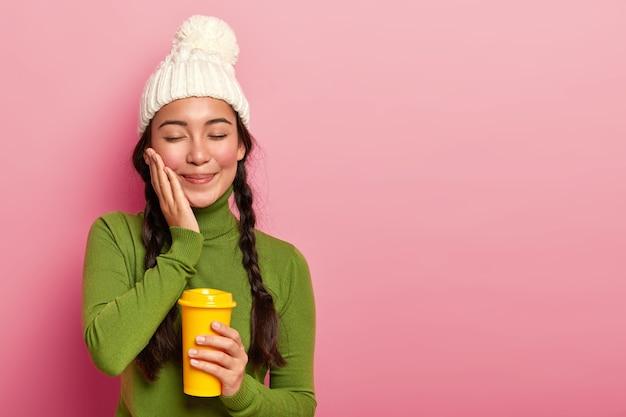 Mulher jovem e bonita bebe bebida aromática de um copo descartável, toca ruge na bochecha, tem aparência suave, usa roupas quentes, isolada sobre fundo rosa