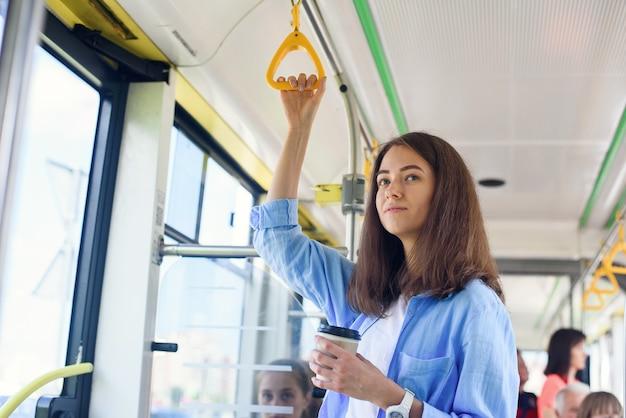 Mulher jovem e bonita bebe café delicioso no ônibus da cidade ou bonde. conceito de transporte público.