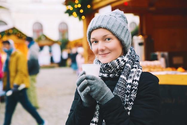 Mulher jovem e bonita bebendo chá de gengibre quente ou vinho quente na xícara no mercado de natal
