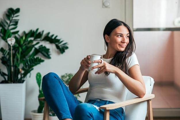 Mulher jovem e bonita bebendo chá em casa. olhando para longe.