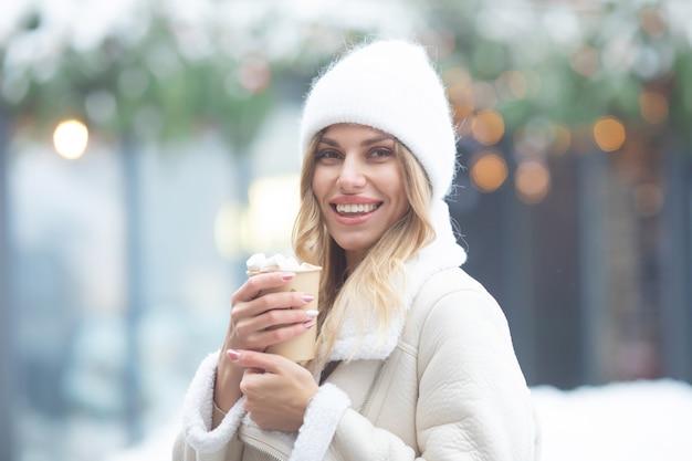 Mulher jovem e bonita bebendo chocolate quente ao ar livre. xmas.