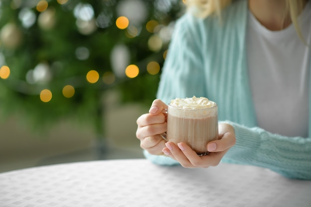 Mulher jovem e bonita bebendo chocolate quente em casa na véspera de natal, closeup